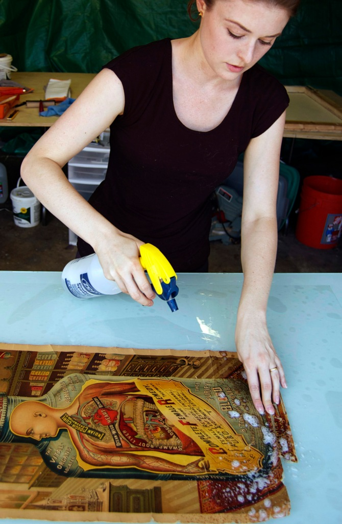 Melissa begins by spraying a gentle soap on the surface of the poster. This makes the paper more permeable to water.