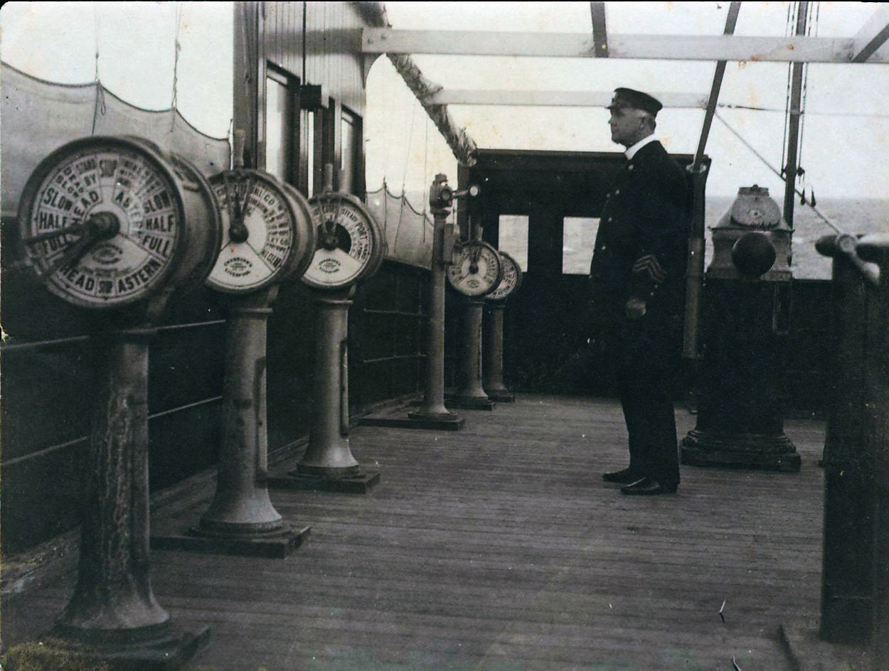Captain,_possibly_W_L_Smith,_standing_on_the_bridge_of_a_steamship_(7647081976)